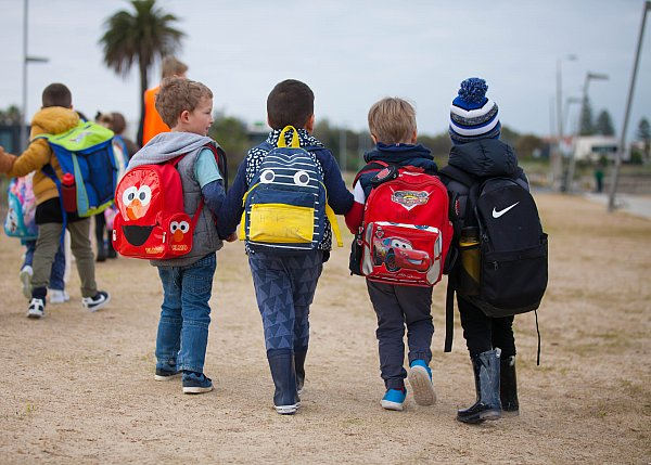 kinder children walking with backpacks